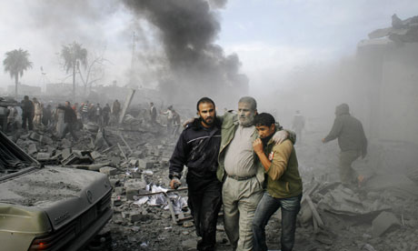 An injured Palestinian is helped from the rubble following an Israeli missile strike in the Gaza Strip on Saturday 27 December, 2008. Photograph: Hatem Omar/AP