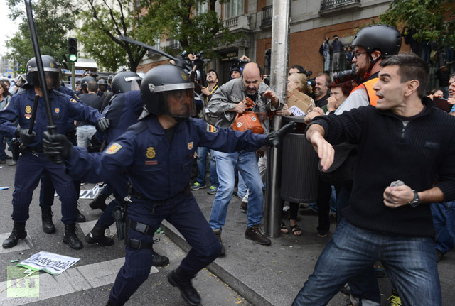 "Spain's ""indignados"" (the outraged ones) clash with police in what seems now like a constant tug of war between an increasingly repressive status quo and the ""99%"". With Spanish youth now facing 50% effective unemployment, the bankruptcy of the ""free enterprise system"" is becoming clear to most rational observers."