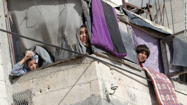 Palestinians peer out into the street to observe results of some rockets. How does life continue under such extreme circumstances?