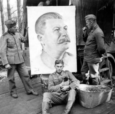 An unusual photograph showing German soldiers in the USSR, before a portrait of Stalin left behind by retreating Soviet troops. The eerie tranquility, accentuated by the puppy, make this a