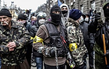 "Members of the fascist ""Patriots of Ukraine"" organization gather for battle on the streets of Kiev, 2014. The yellow armbands display the group's symbol, a repurposed Nazi rune known as the ""Wolfsangel."" Photographer unknown."