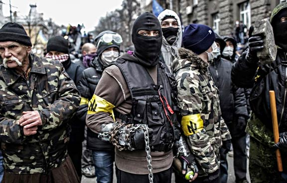 """Members of the fascist """"Patriots of Ukraine"""" organization gather for battle on the streets of Kiev, 2014. The yellow armbands display the group's symbol, a repurposed Nazi rune known as the """"Wolfsangel."""" Photographer unknown."""