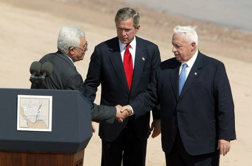 Palestinians president M. Abbas shaking hands with Sharon, with Bush2 hosting the charade.