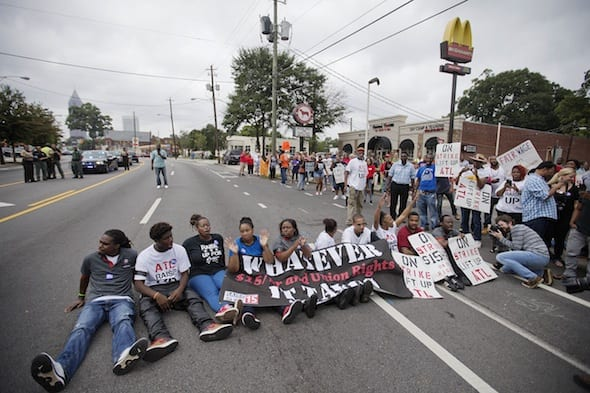 Protesters block Atlanta's Ponce de Leon Avenue on Thursday outside a McDonald's restaurant. They were demanding that fast food chains pay workers at least $15 an hour. AP/David Goldman