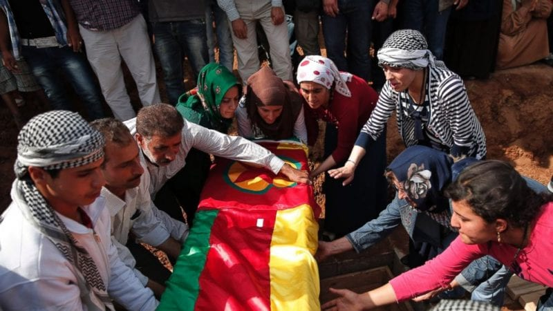 Mourners lower the coffin bearing the body of Mizgin Culbakge, a female Kurdish fighter killed in clashes with militants of the Islamic State group in Kobani, Syria, during the funeral of four female fighters, at a cemetery in Suruc, on the Turkey-Syria border, Tuesday, Oct. 14, 2014. Kobani, also known as Ayn Arab, and its surrounding areas, has been under assault by extremists of the Islamic State group since mid-September and is being defended by Kurdish fighters. (AP Photo/Lefteris Pitarakis) Close