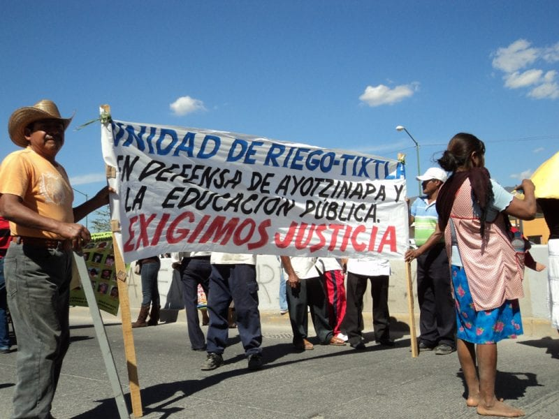 """We demand Justice"" proclaims the banner held by local villagers. (click to enlarge)"