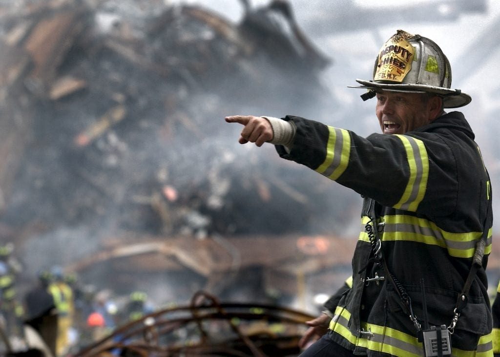 010914-N-3995K-003 New York, N.Y. (Sept. 14, 2001) -- Retired Fire Chief Joseph Curry barks orders to rescue teams as they clear through debris that was once the World Trade Center.  U.S. Navy Photo by Journalist 1st Class Preston Keres.  (RELEASED)