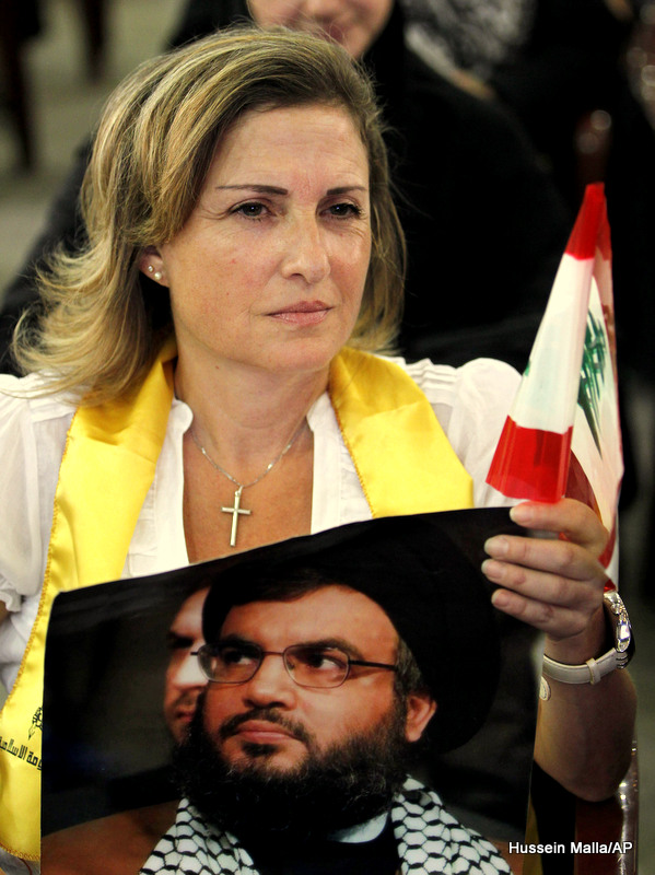 A Christian woman supporter of Hezbollah, carries a picture of Hezbollah leader Hassan Nasrallah along a Lebanese flag as she listens to Nasrallah's speech in the occasion of Jerusalem Day in the southern suburb of Beirut, Lebanon, Friday, Sept. 3, 2010. Hezbollah leader says he will not respond to a U.N.-appointed prosecutor's demand for his group to hand over all information relevant to the assassination case of former Lebanese Premier Rafik Hariri. Sheik Hassan Nasrallah says the group is ready to cooperate instead with the Lebanese judiciary.