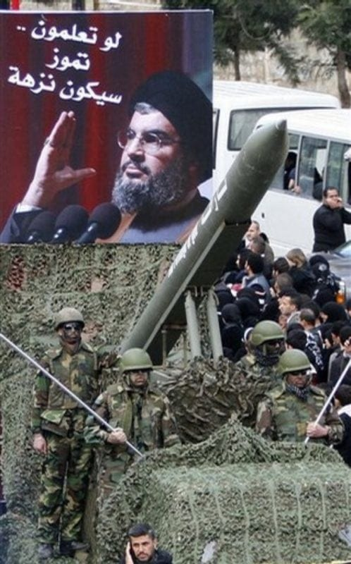 "Lebanese Hezbollah fighters stand next to a mock rocket under a poster of Hezbollah's leader Sheik Hassan Nasrallah with arabic words reading:"" To let you know, July (2006 war) was a picnic,"" during a demonstration to protest Israel's attack on the Gaza Strip, in the southern market town of Nabatiyeh, Lebanon, on Saturday Jan. 10, 2009. Nearly 20,000 demonstrators marched through the streets of the market town of Nabatiyeh in a rally organized by Hezbollah."