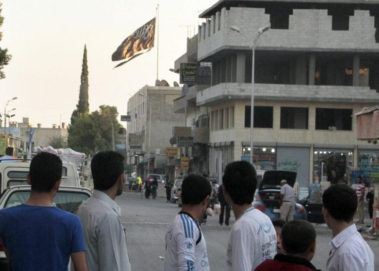 Group of men look at large ISIS flag flying over building in Raqqa.