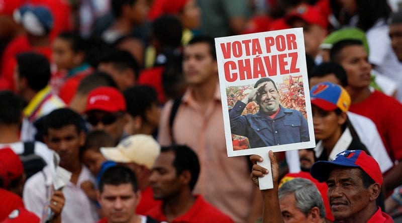 """A supporter of Venezuela's President Nicolas Maduro holds a poster with a picture of late Venezuelan President Hugo Chavez that reads """"Vote for Chavez"""" during the last campaign rally with pro-government candidates for the upcoming parliamentary elections, in Caracas © Carlos Garcia Rawlins / Reuters"""