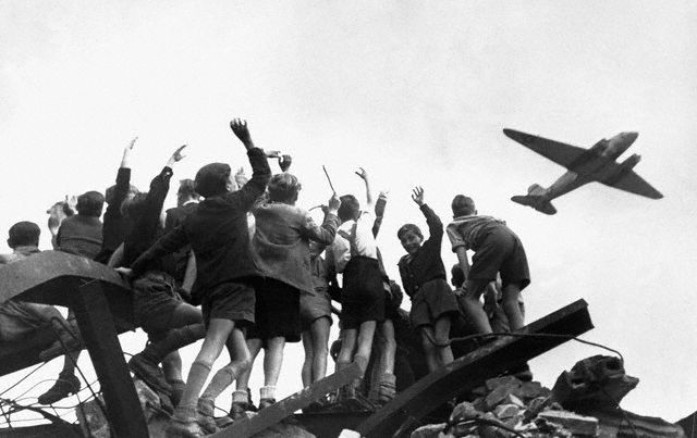 1948, West Berlin, Germany --- Children perched atop war debris in West Berlin wave to an American cargo plane bringing food and supplies during the Soviet Union's blockade of the city in 1948. --- Image by © Bettmann/CORBIS