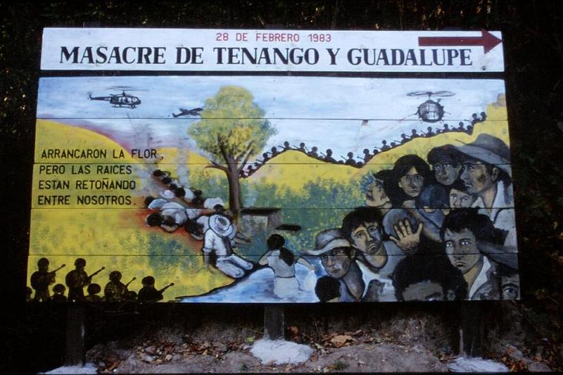 "A billboard serving as a reminder of one of many massacres that occurred during the Civil War in El Salvador. The Castilian inscription to the left reads in English: ""They tore out the flower, but the roots are returning among us."" (Dave Watson)"