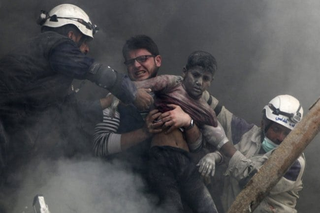 ATTENTION EDITORS - VISUAL COVERAGE OF SCENES OF INJURY OR DEATH Men rescue a boy from under the rubble after what activists said was explosive barrels dropped by forces loyal to Syria's President Bashar Al-Assad in Al-Shaar neighbourhood of Aleppo April 6, 2014. REUTERS/Hosam Katan (SYRIA - Tags: POLITICS CIVIL UNREST CONFLICT TPX IMAGES OF THE DAY) - RTR3K52P