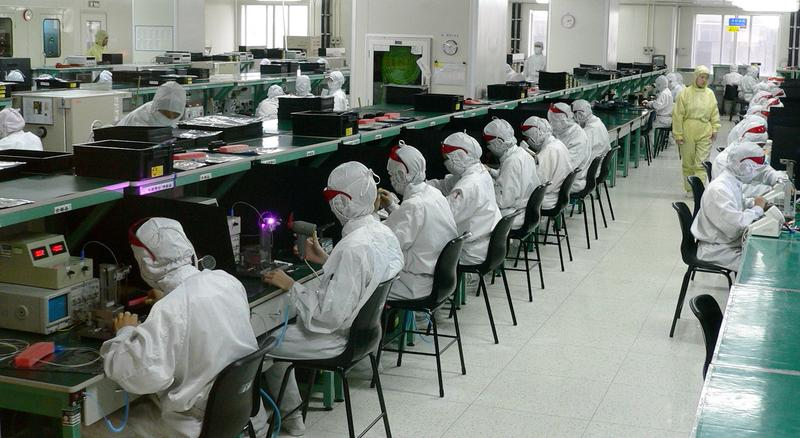 "Foxconn workers assembling iPhones in one of the firm's several self-contained ""campuses"" in China. The company is Taiwanese owned, and currently"