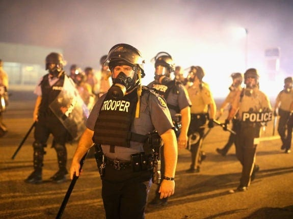 FERGUSON, MO - AUGUST 17:  Police advance through a cloud of tear gas toward demonstrators protesting the killing of teenager Michael Brown on August 17, 2014 in Ferguson, Missouri.