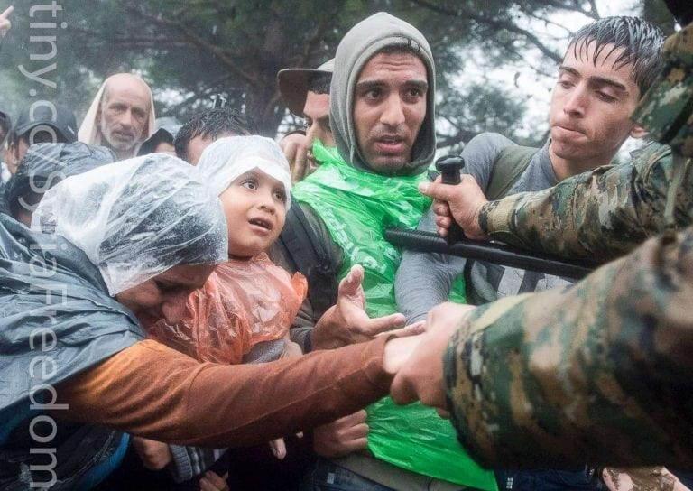 Refugees helped by Macedonian Police. Freedom House.)