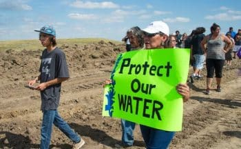 CORRECTION - A protest holds a sign reading Protect Our Water as Native Americans and their supporters walk on land designated for the Dakota Access Pipeline (DAPL), after protestors confronted contractors and private security guards working on the oil pipeline project, forcing them to retreat, September 3, 2016, near Cannon Ball, North Dakota. Hundreds of Native American protestors and their supporters, who fear the Dakota Access Pipeline will polluted their water, forced construction workers and security forces to retreat and work to stop. / AFP / Robyn BECK / The erroneous mention[s] appearing in the metadata of this photo by Robyn BECK has been modified in AFP systems in the following manner: [A protest holds a sign reading Protect Our Water as Native Americans and their supporters walk on land designated for the Dakota Access Pipeline (DAPL), after protestors confronted contractors and private security guards working on the oil pipeline project, forcing them to retreat, September 3, 2016, near Cannon Ball, North Dakota.] instead of [A protestor is treated after being pepper sprayed by private security contractors on land being graded for the Dakota Access Pipeline (DAPL) oil pipeline, near Cannon Ball, North Dakota, September 3, 2016.]. Please immediately remove the erroneous mention[s] from all your online services and delete it (them) from your servers. If you have been authorized by AFP to distribute it (them) to third parties, please ensure that the same actions are carried out by them. Failure to promptly comply with these instructions will entail liability on your part for any continued or post notification usage. Therefore we thank you very much for all your attention and prompt action. We are sorry for the inconvenience this notification may cause and remain at your disposal for any further information you may require. (Photo credit should read ROBYN BECK/AFP/Getty Images)