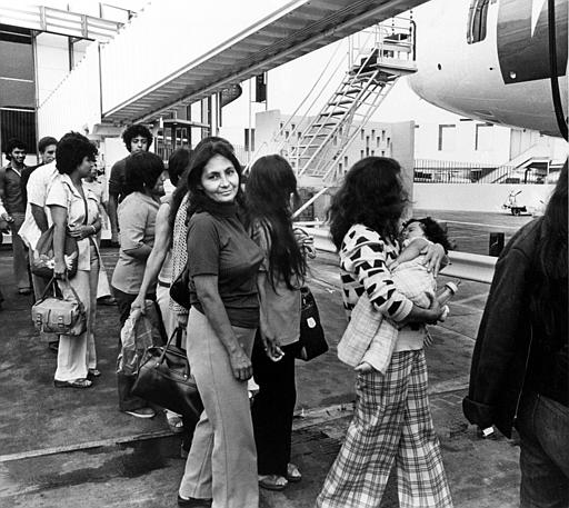 Illegal Mexican immigrants, among them a woman carrying a baby, are boarding a plane in Los Angeles, Calif., as they are being deported back to their native Mexico, July 27, 1976. (AP Photo)