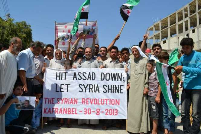 Anti-Assad rebels demonstrating in Northern Syria: Note the factory fresh flags. Who provided them?
