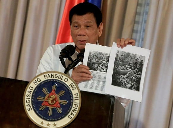 President Rodrigo Duterte shows images of the Bud Dajo massacre during his speech at the 2016 Metrobank Foundation's Outstanding Filipinos awarding ceremony in Malacañan's Rizal Hall on September 12. REY BANIQUET/PPD