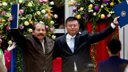 FILE - In this June 14, 2013 file photo, President Daniel Ortega, left, and Chinese businessman Wang Jing hold up a concession agreement for the construction of a multibillion-dollar canal at the Casa de los Pueblos in Managua. Nicaragua's government and China's HKND Group on Monday July 7, 2014, unveiled the route of a proposed inter-ocean canal to compete with the Panama Canal that Sandinista officials hope with lift the Central American country out of poverty. (AP Photo/Esteban Felix, File)