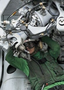Mechanic fixing a problem on a chopper aboard the USS Nimitz.  America's weapons are extremely complex, a weakness in tactical terms.
