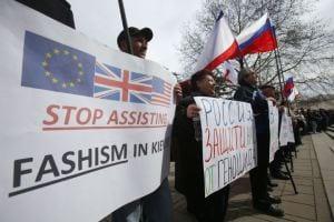 "Pro-Russian demonstrators in Crimea denounce Fascists in Kiev regime. ""Stop Assisting Fascists"" read some of the signs."