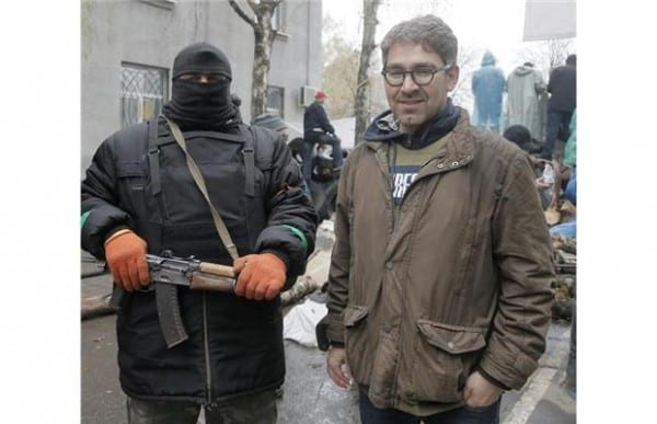 Western journalist standing by pro-Russia activist in Slavyansk, Eastern Ukraine.