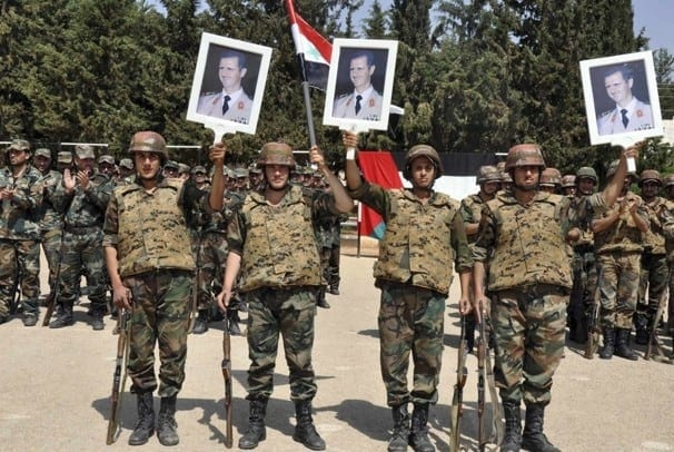 Syrian army regulars celebrating a recent victory and hailing Assad.