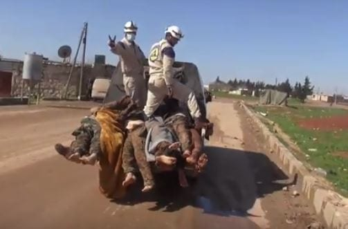 VIDEO STILL: 'Neutral' White Helmet operatives flash the victory sign as they cart off dead Syrian Army corpses.