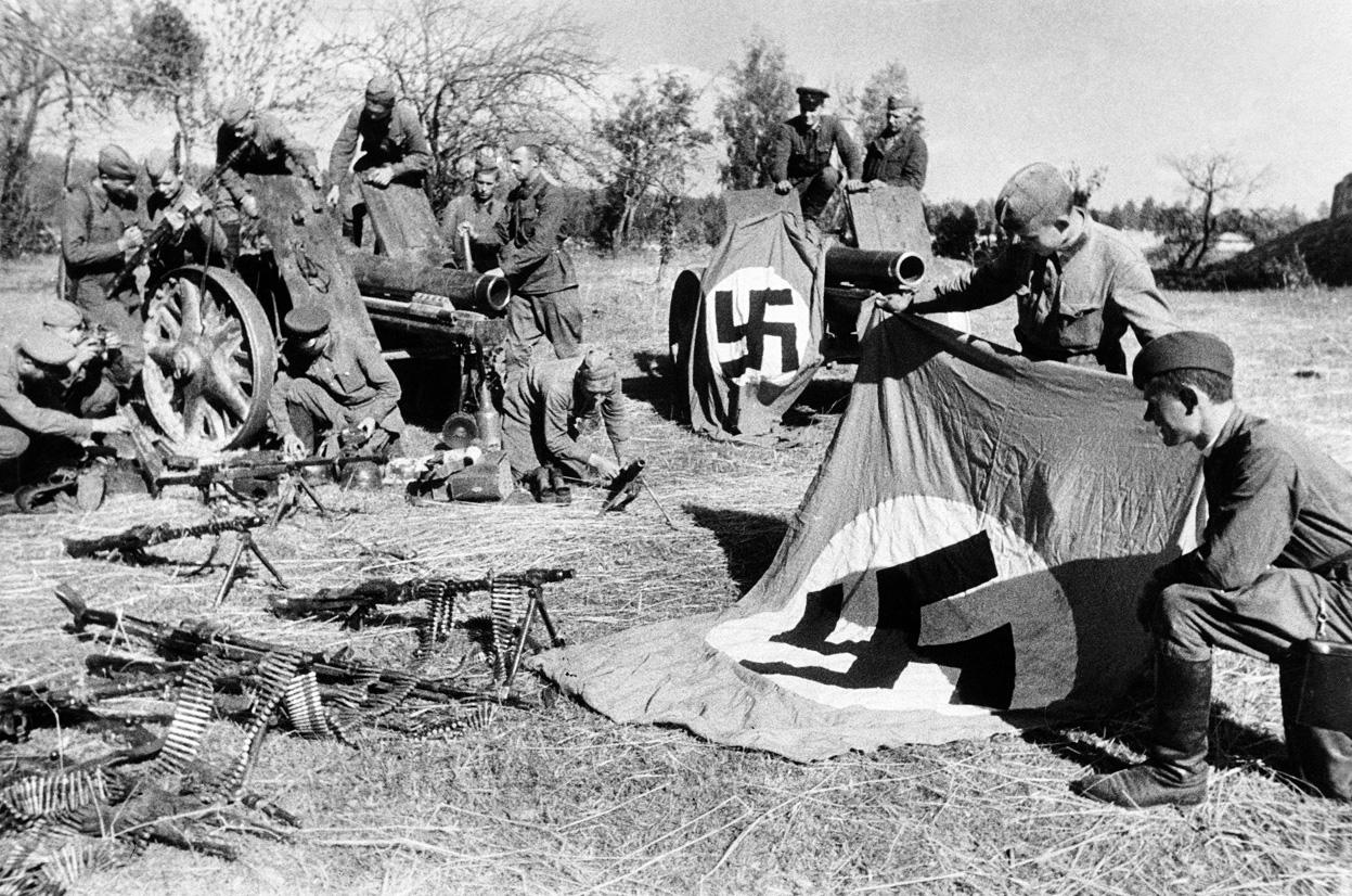 Soviet soldiers examine captured Nazi weapons.