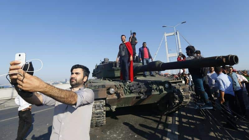 Erdogan supporter taking selfie before a surrendered tank.