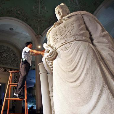"""SHANGHAI, CHINA - JULY 6: (CHINA OUT) A worker inspects a statue of Chinese ancient voyager Zheng He (1371-1435), preparing for the """"Zheng He Ocean Voyages Exhibition & International Marine Expo"""" on July 6, 2005 in Shanghai, China. The exhibition and expo will be held on July 8 in Shanghai to mark the 600th anniversary of the voyager's epic journey. Various activities are being held in China to celebrate the anniversary of Zheng's seven voyages, in which he sailed from China to more than 30 countries and regions throughout the Indian Ocean and Persian Gulf from 1405 to 1433. (Photo by China Photos/Getty Images)"""